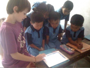 Jude showing the children in India how to use the iPad